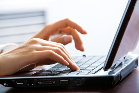 Image of female hands on the keys typing documents